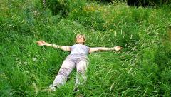Happy woman lying on green grass in a meadow Stock Footage