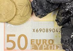 fifty euro banknote with euro coins and raw coal nuggets - stock photo