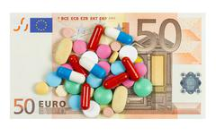 fifty euro banknote whith pills on it isolated on white background - stock photo