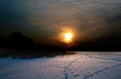 sunset over lake in winter - stock photo