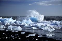 An iceberg being broken by the waves Stock Photos
