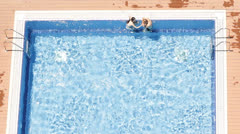 Aerial view of sexy young couple relaxing and swimming pool summer time Stock Footage