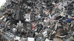 Crane sorting through scrap metal at scrapyard united kingdom Stock Footage