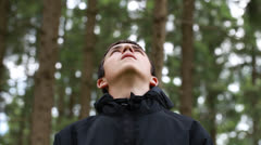 Lost boy staring at the treetops Stock Footage