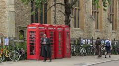 Professor in black gown uses mobile phone, Cambridge, England Stock Footage