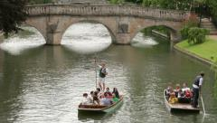 People punting on river cam with clare bridge in background, cambridge Stock Footage
