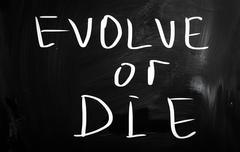 """evolve or die"" handwritten with white chalk on a blackboard - stock illustration"