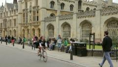 Female graduate in black gown cycles past kings college, cambridge, england Stock Footage