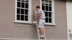 Male painter on ladder paints shop window frame white Stock Footage