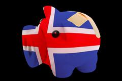 bankrupt piggy rich bank in colors of national flag of iceland    closed with - stock photo