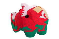 Closed piggy rich bank with bandage in colors national flag of wales Stock Photos