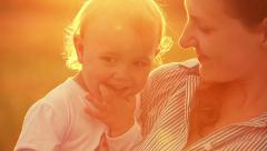 Happy mother with little daughter at sunset (close-up) - stock footage