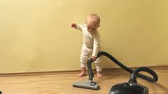 Active baby cleaning with vacuum cleaner  the floor Stock Footage