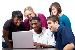 Multi-racial college students sitting around a computer Stock Photos