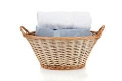 white and blue towels in a laundry basket on white - stock photo
