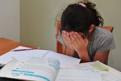 Young girl struggles with her homework Stock Photos