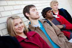 multi-racial college students against a brick wall - stock photo