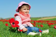Baby girl sitting in flowery field Stock Photos