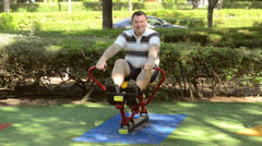 Fat man on a rowing machine outdoor Stock Footage