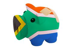 closed piggy rich bank with bandage in colors national flag of south africa - stock photo