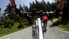 Mountainbiker riding down on main road Stock Footage