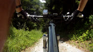 Stock Video Footage of Mountainbiker riding down dirt road