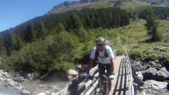 Mountainbiker crossing bridge in Savognin, Switzerland Stock Footage
