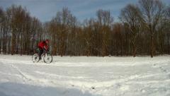 Mountain biker riding through snow Stock Footage