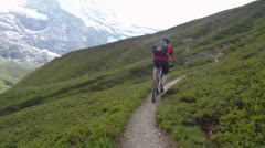 Mountain biker riding downhill on small dirt road Stock Footage