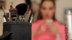 Make up of unknown woman with make up brushes in foreground Stock Footage