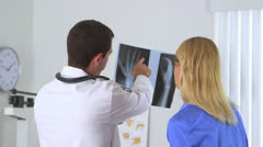 Doctor reviewing x-ray with patient Stock Footage
