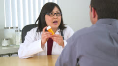 Asian doctor giving prescription medicine to patient - stock footage