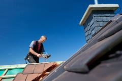 Roofer molding tiles with a hammer Stock Photos