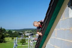 Roofer applying slates Stock Photos