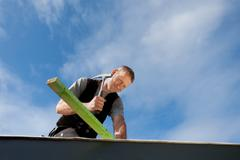 roofer hammering a nail - stock photo