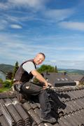 happy roofer working on a roof tile - stock photo