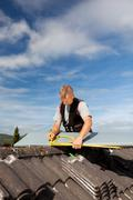 Roofer working with an angle ruler on a rooftop Stock Photos