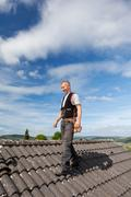 Roofer walking over an old roof Stock Photos