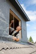 roofer taking measures for a new window - stock photo