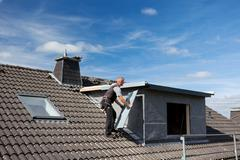 Roofer carrying a metal piece to the dormer Stock Photos