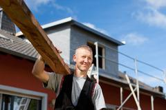 roofer carrying a wood plank over his shoulder - stock photo