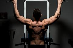 Young male bodybuilder doing heavy weight exercise Stock Photos