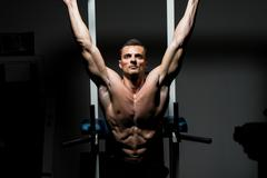 Handsome man exercising his abs at the gym Stock Photos