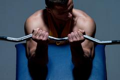 Stock Photo of fitness trainer doing heavy weight exercise for biceps