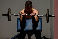 fitness trainer doing heavy weight exercise for biceps - stock photo