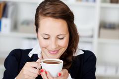 woman enjoying a cup of coffee - stock photo