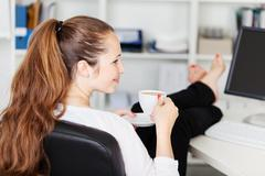 woman taking a coffee break in her office - stock photo