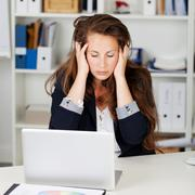 Unhappy woman sitting in her office Stock Photos