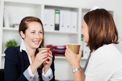 Women executives during a coffee break Stock Photos