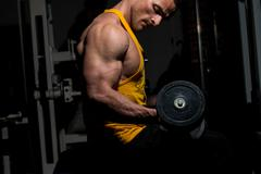 Young man doing heavy weight exercise for biceps Stock Photos